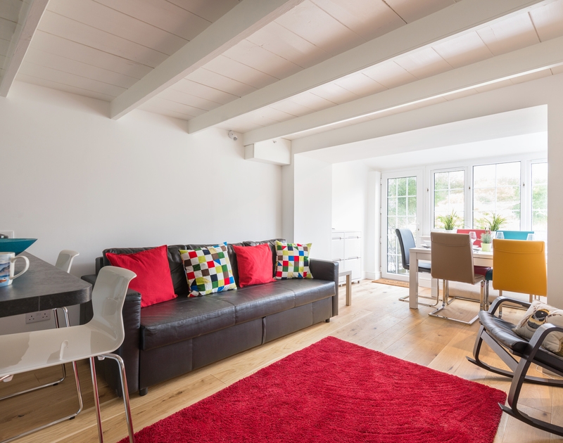 The open plan living area has exposed beams and warm wooden flooring at recently refurbished Beehive Cottage, a self catering holiday retreat in picturesque Port Isaac on the North Coast of Cornwall.