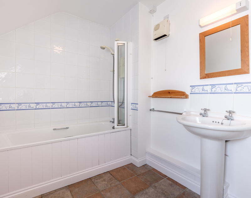 The bathroom with an overhead shower at St Breock, a self catering holiday house to rent in Polzeath.
