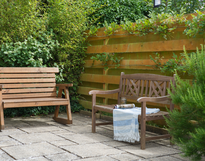 Garden benches in the garden at Curlew, on a sheltered patio area, ideal for reading or enjoying the sunshine.