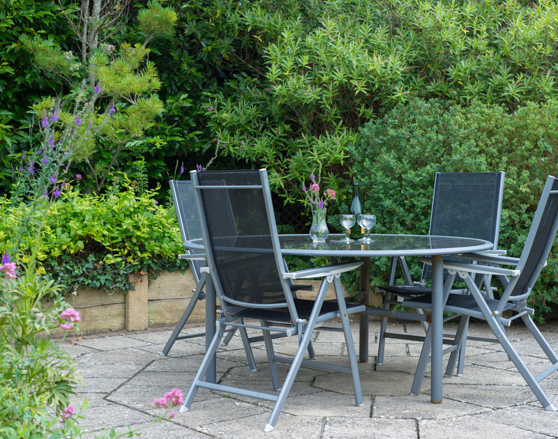 Garden furniture on the paved patio area of the garden at Curlew in Rock.