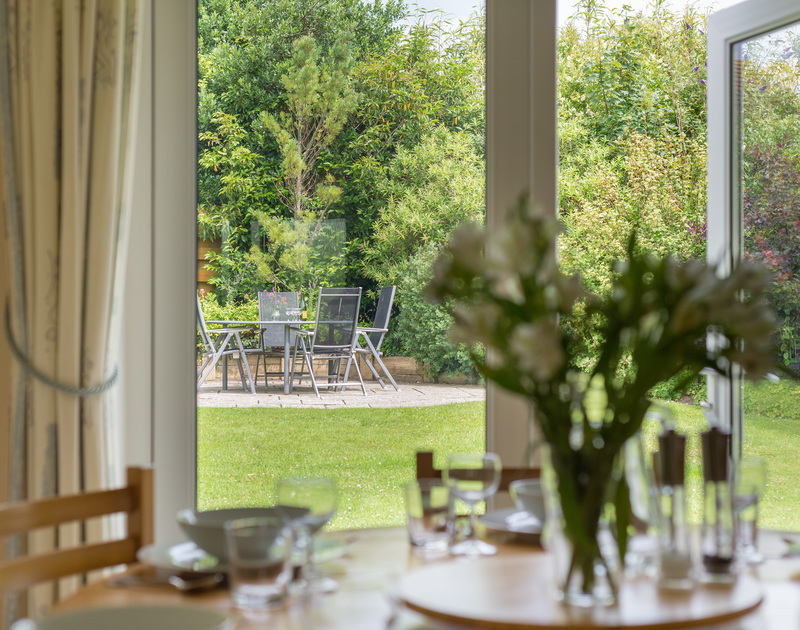 Family meals around the dining table at Curlew with a lovely outlook onto the mature garden in Rock.