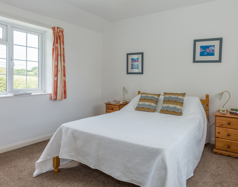 The double bedroom at the White House in Rock, Cornwall has an ensuite shower room and countryside views.