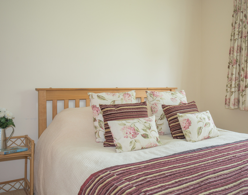 Relax in the pretty king size bedroom at Guelder Rose, a self catering holiday house to rent in Rock, north Cornwall