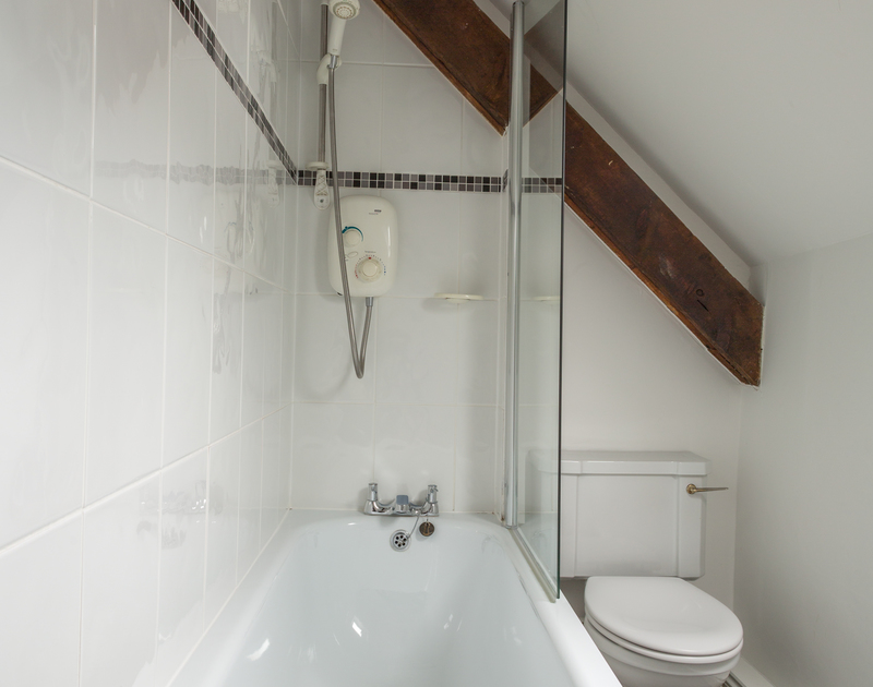 Self catering holiday apartment,Gully Lofts has a white family bathroom suite with a shower over the bath and vaulted beamed ceilings in Port Isaac, Cornwall.