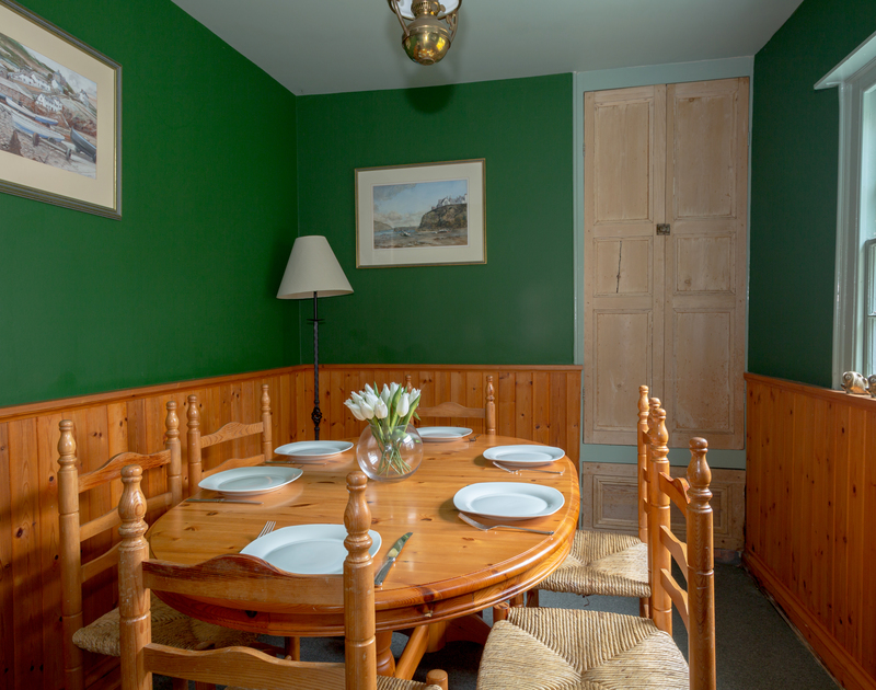 Cosy dining room of Quay Cottage, a holiday rental in Port Isaac, Cornwall with wood panelling and wide sash window.