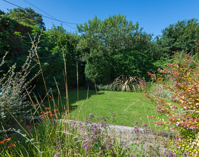 The pretty secluded garden with a lawn at holiday cottage Conifers to rent in Rock.