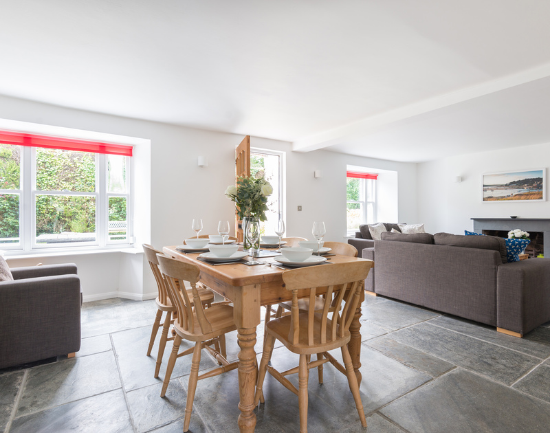 The dining table on the gorgeous slate floor in the open plan sitting/dining room at Conifers, a holiday house to rent in Rock.