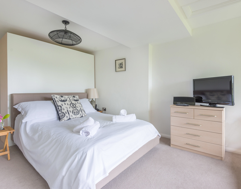 The double bedroom at Conifers with an ensuite shower room and a balcony overlooking the garden.