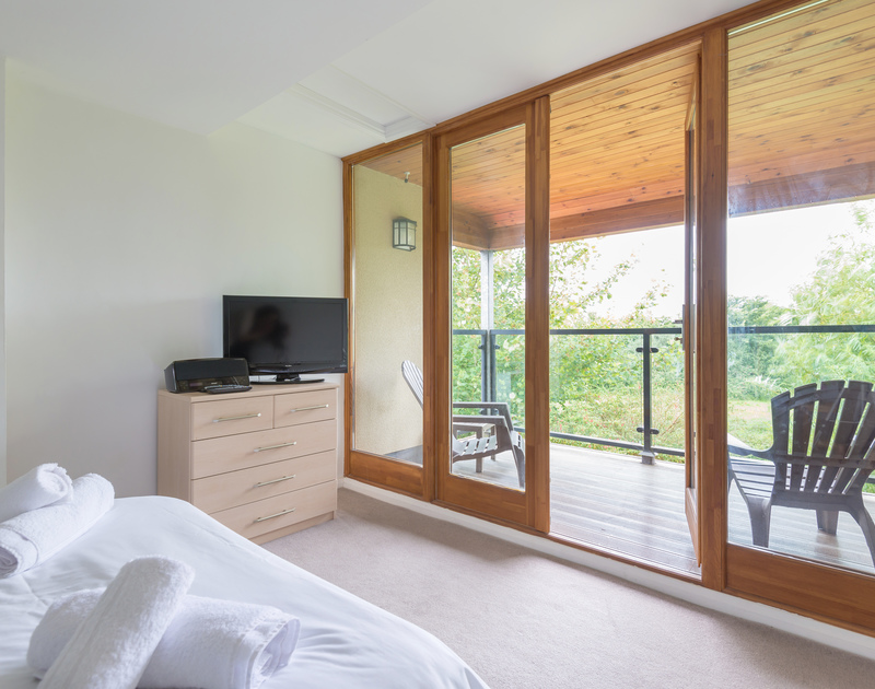 The french doors leading out from one of the double bedrooms onto a decked balcony overlooking the garden at self catering, holiday house to rent in Rock.