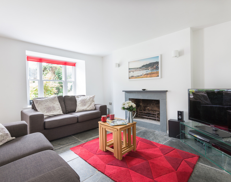 The comfortable and elegant lounge with an open fire in Conifers, a self catering holiday house to rent in Rock on the north coast of Cornwall.