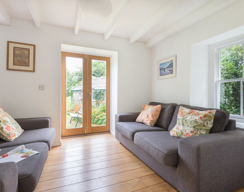 Two comfortable sofas and useful french windows in Conifers, a self catering holiday house to rent in Rock, North Cornwall.