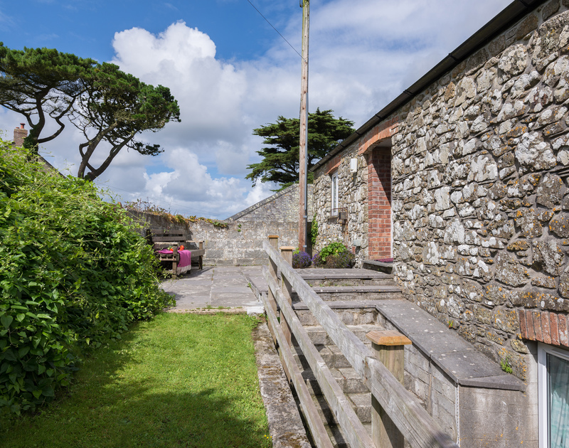 Slate flagged, suntrap patio area at self catering barn conversion An Skyber Barn in Trelights, North Cornwall.