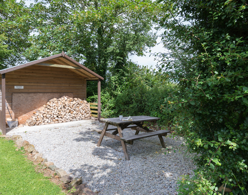 Covered wood store outside at An Skyber Barn with a picnic table on a sheltered area of gravel.