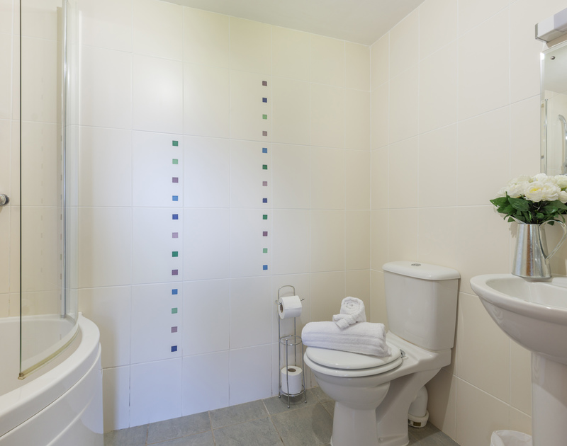 The family bathroom with overhead shower in the pretty converted barn An Skyber.