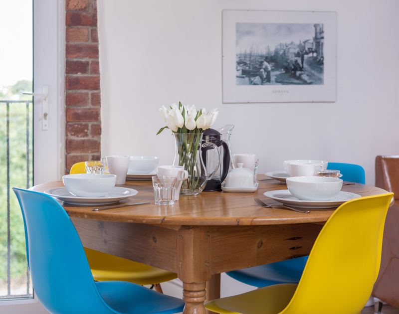 A sociable, round dining table in the open plan kitchen, dining, living room in An Skyber Barn.