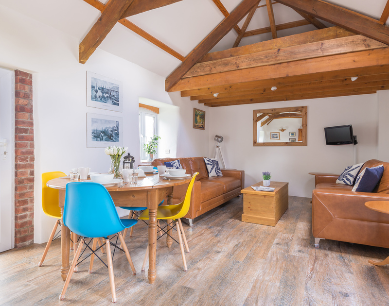 The attractive and exposed beams emphasis the size and space of the vaulted ceiling in An Skyber Barn, a holiday rental in Trelights, close to Port Isaac in Cornwall.