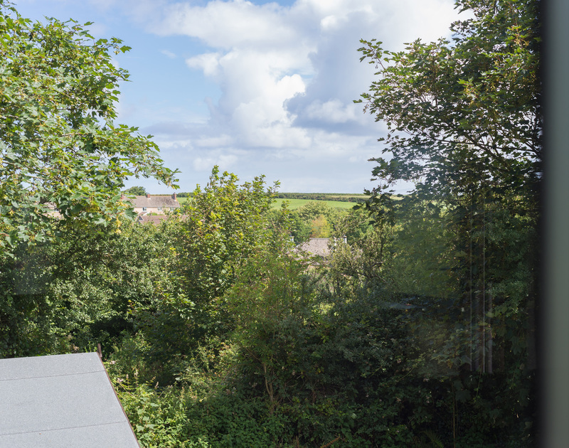Glimpses of the pretty village of Trelights through the trees from the elevated setting of self catering holiday house An Skyber Barn.