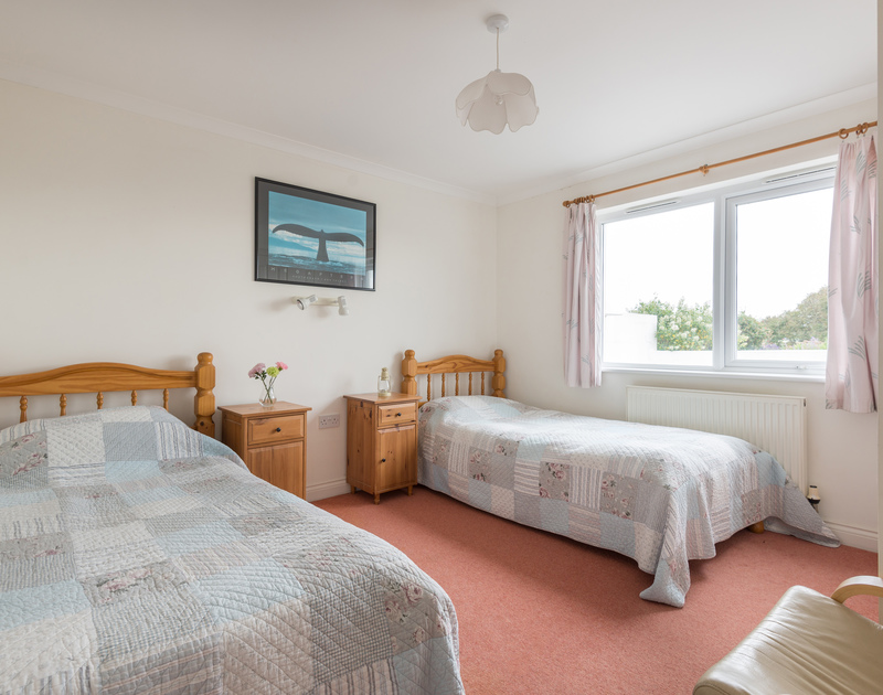 The twin bedroom at Kirra, a self-catering holiday house in Polzeath, Cornwall, with its matching quilts.