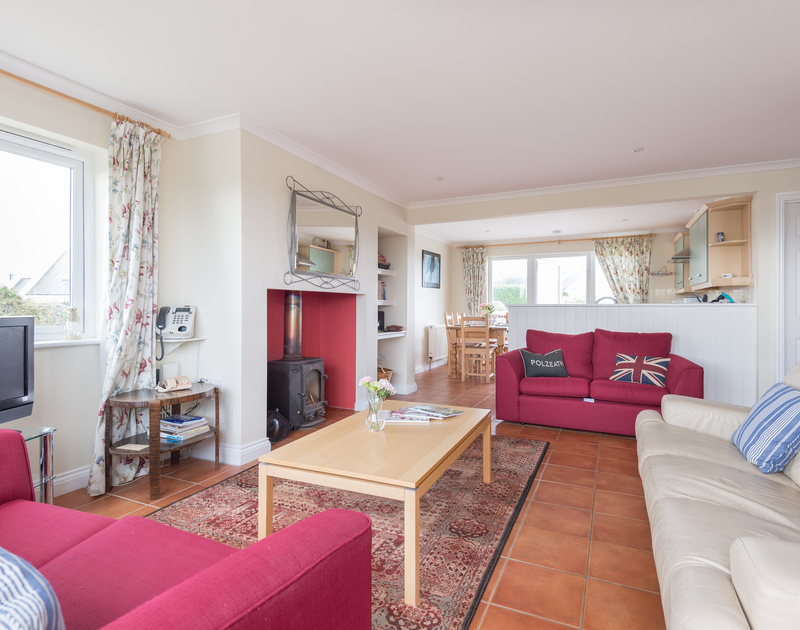 Relax with the family in the open plan sitting room at Kirra, a holiday house at Polzeath, Cornwall, with patio doors to the garden.