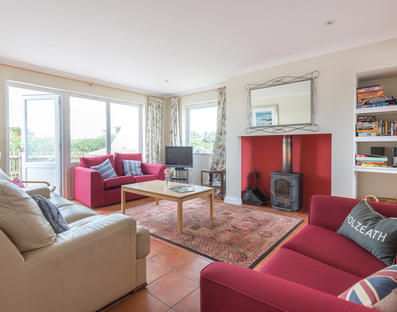 The sitting room at Kirra, a holiday house in Polzeath, Cornwall has a cosy wood burning stove and access onto the garden and patio.