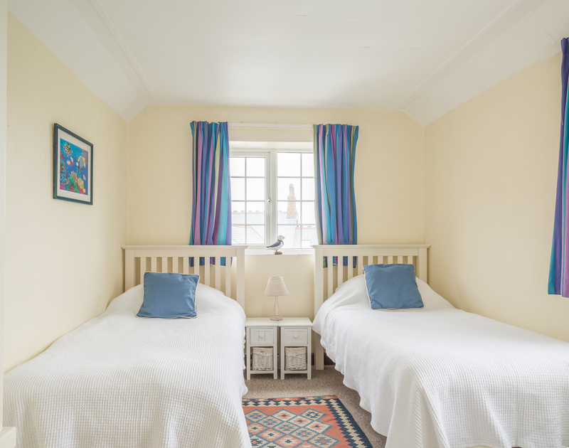 A twin bedroom in the annexe of Ivy cottage, a holiday house in Polzeath, North Cornwall