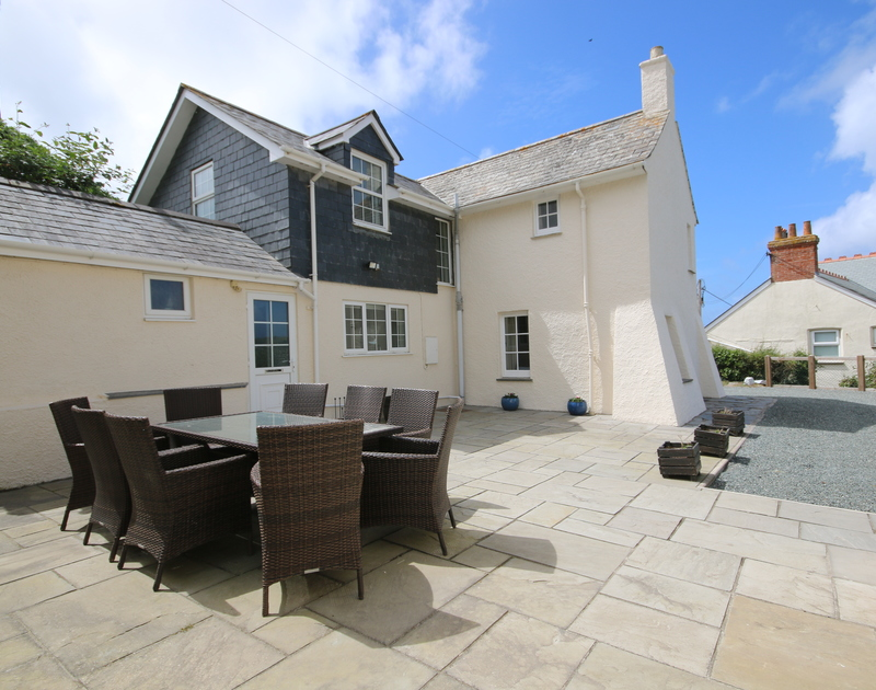 The exterior view of Ivy Cottage and its sunny terrace, a holiday rental in Polzeath, North Cornwall