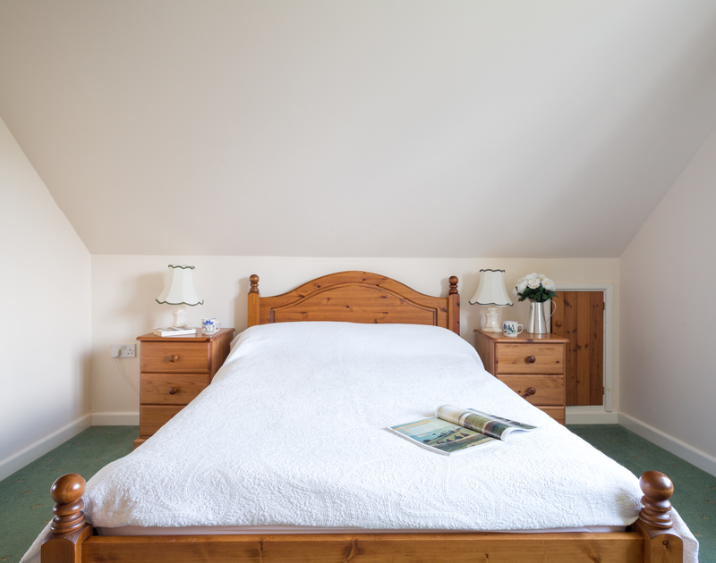 Attractive double bedroom at Haven Cottage, a self-catering holiday cottage in Port Isaac, Cornwall, with pine furniture.