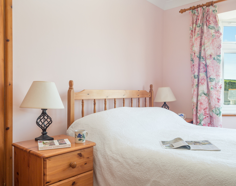 Ground-floor ensuite double bedroom at Haven Cottage, a holiday cottage in Port Isaac, Cornwall, with pine wardrobe and dressing table.