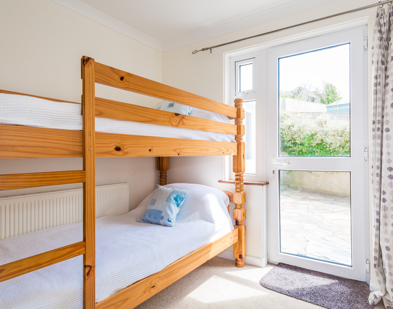 The bunk bedroom with direct access onto the rear patio at Shilling Stones, a holiday rental in Port Isaac