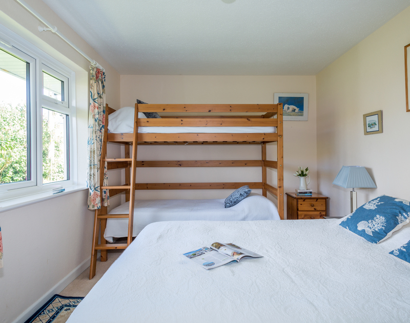 Master bedroom with a king sized bed, bunk beds and window overlooking the side garden in self catering holiday bungalow Caelum, in Port Isaac, North Cornwall.