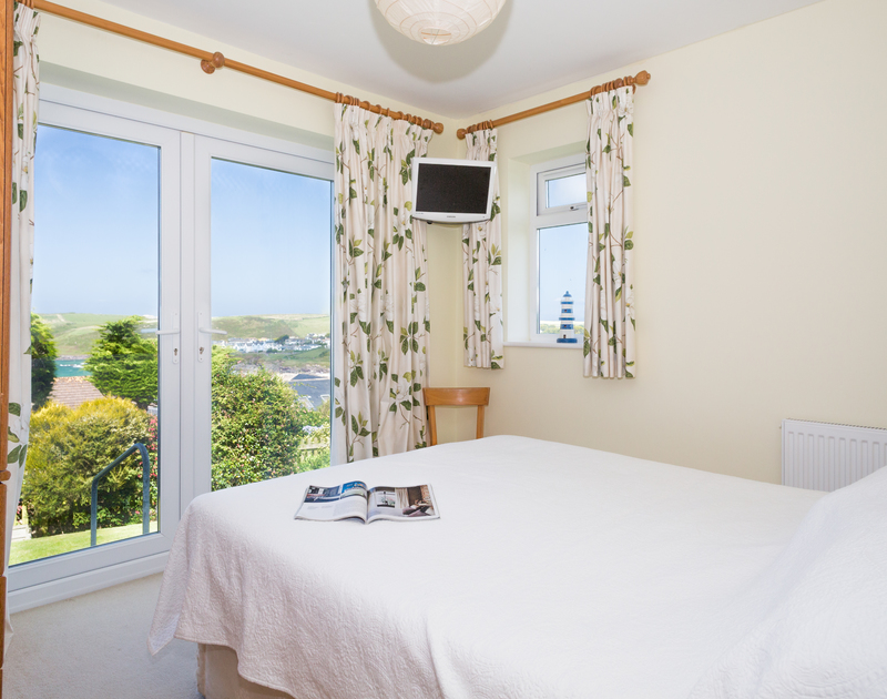The king size bedroom with views down the garden, over the sea to the headland of Pentire Point from Trevic in Polzeath.