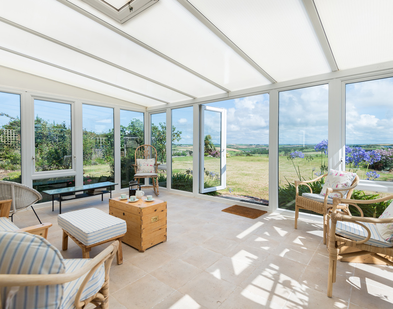 Have morning coffee and enjoy the far reaching rural views from the large, light filled conservatory at Treperran in Trebetherick in North Cornwall.