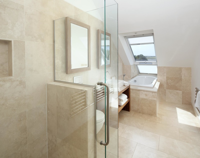 The master bedroom ensuite at Greenaway Reach near Daymer Bay, Cornwall has both a bath and shower with stunning sea views