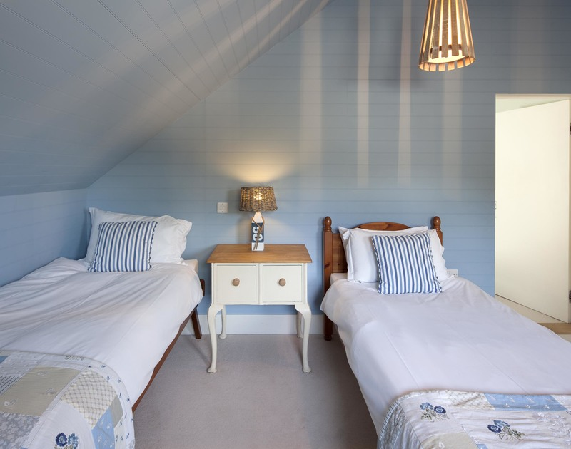 Bedroom 5 at Geenaway Reach near Daymer Bay, north Cornwall has twin beds and shared access to a shared family bathrom