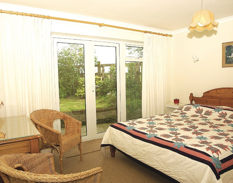 The pretty king size bedroom with french windows out to the garden at Little Pityme, a self catering holiday house to rent in Rock, Cornwall.
