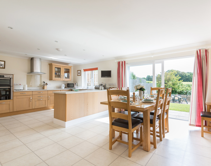 The modern, practical kitchen at Willowbrook, an attractive holiday house to rent in Rock, Cornwall, with sliding doors to the garden.