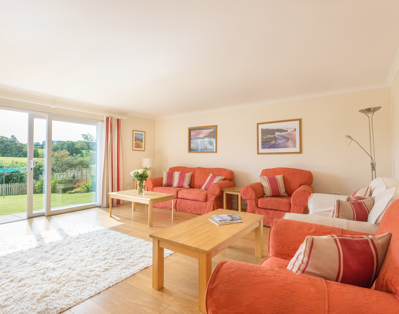 The light, spacious lounge of Willowbrook, a holiday rental in Rock, Cornwall, with sliding doors to the garden.