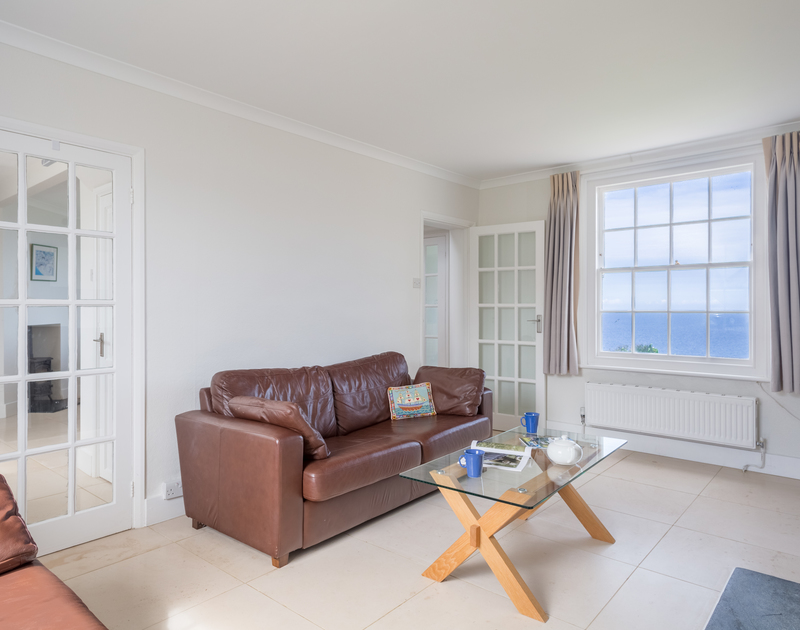 Comfortable leather sofas and an open fire in the sitting room at Coastguard cottage 3, a seafront, self catering holiday house to rent in Port Isaac, North Cornwall.