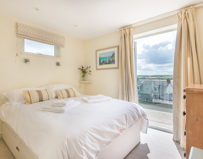 Light double bedroom with kingsize bed and doors to balcony at Slipway 23, a holiday cottage in Rock, Cornwall