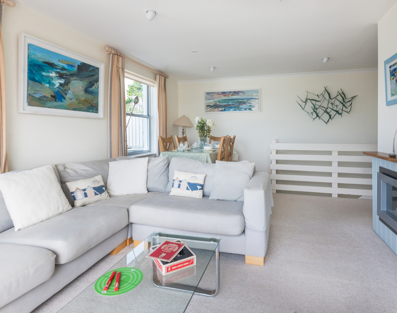 Seascape paintings adorn the walls in the sitting room at self catering holiday house Slipway 23, in Rock, Cornwall.