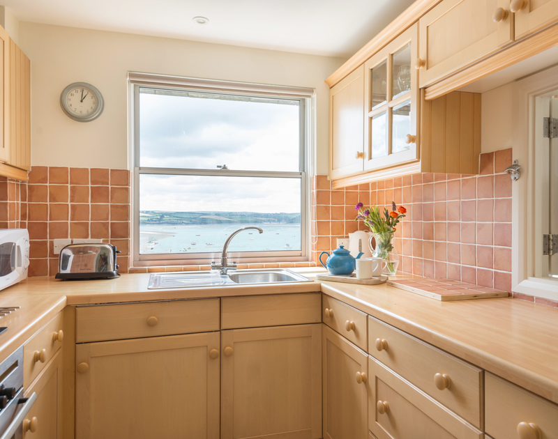 Sea views from the window of this light, compact kitchen at Slipway 23, holiday cottage in Rock, Cornwall