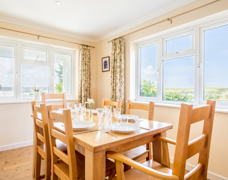 The light filled dining room at Higher Crawallis set above Daymer Bay in Cornwall.