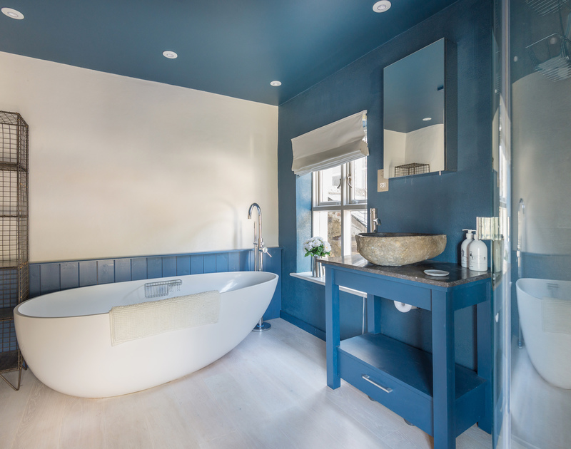 Cool blue colours and a freestanding bath in the deluxe bathroom at self catering holiday accommodation Creel Cottage in Port Isaac in Cornwall.