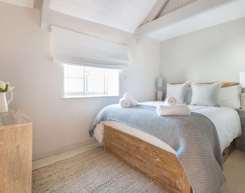 Funky wooden bedstead and matching chest of drawers with cool grey and white decor at self catering holiday retreat Creel Cottage in Port Isaac.