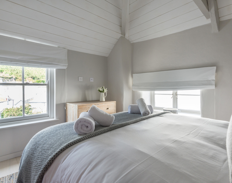 The bedrooms at Creel Cottage have a calming colour palette of white and grey and have views over the village of Port Isaac in North Cornwall.
