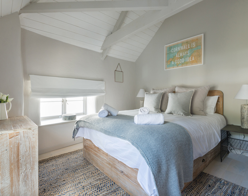 The king sized bedroom at self catering Creel Cottage has gorgeous furnishings and a sense of space and light from the vaulted ceiling and has views over Port Isaac village.