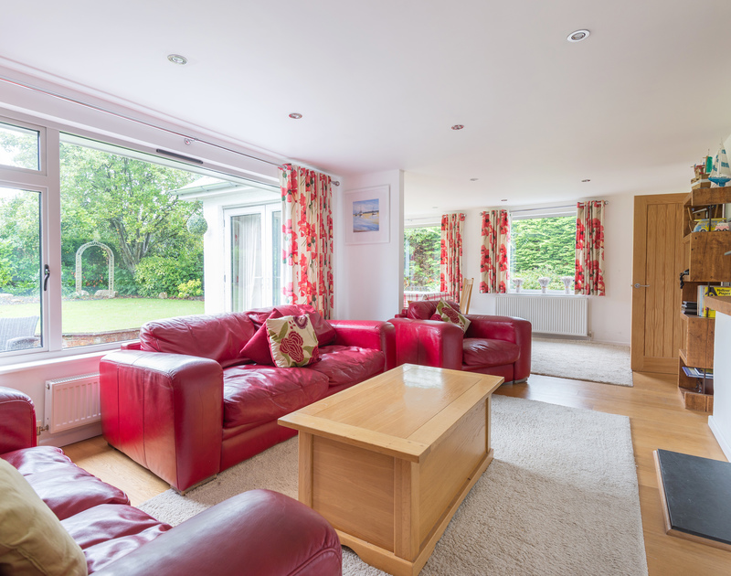 The spacious open plan sitting room at Penolver Lodge, a holiday house in Rock, has a fireplace and overlooks the pretty garden