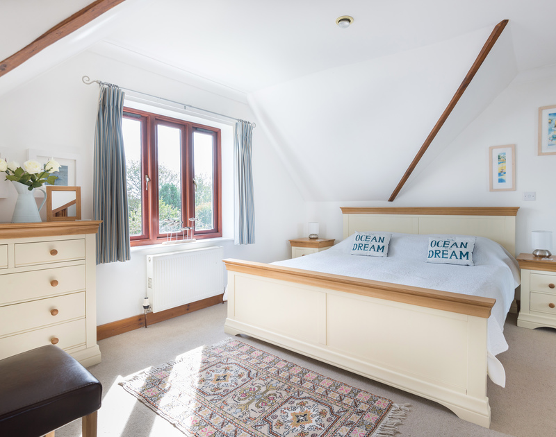 Smart and spacious master bedroom of Gulls Cottage, a holiday house in Rock, Cornwall, with vaulted ceiling.