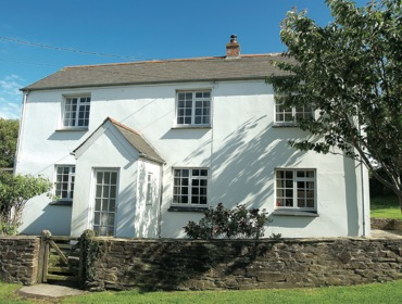 The outside of White House, a charming, white-painted cottage in the hamlet of Tredrizzick, near Rock, Cornwall.