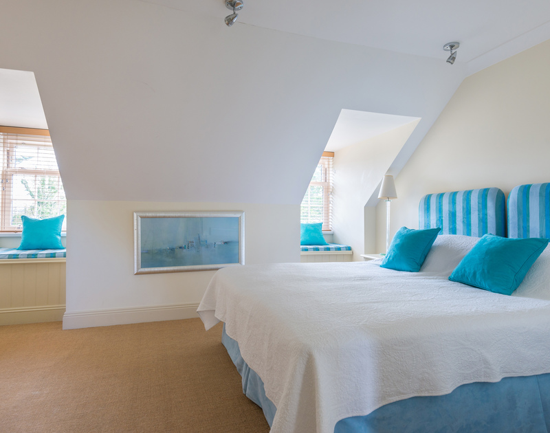 A stylish bedroom at Lowenna Manor 5, a self-catering holiday house in Rock, North Cornwall, with touches of blue furnishings.